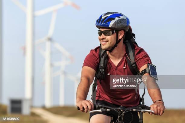 Smiling biker riding in front of wind turbine farm