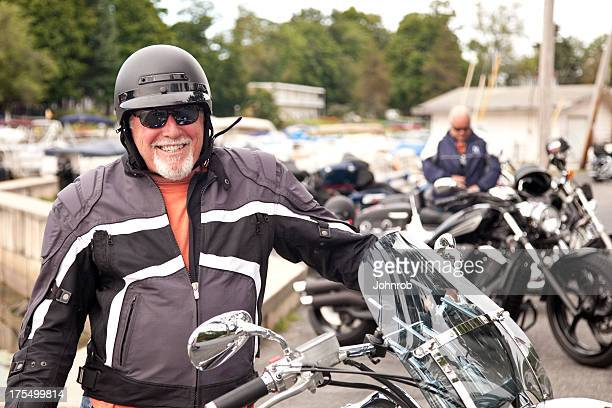 Smiling Biker standing next to motorcycle on a cool day
