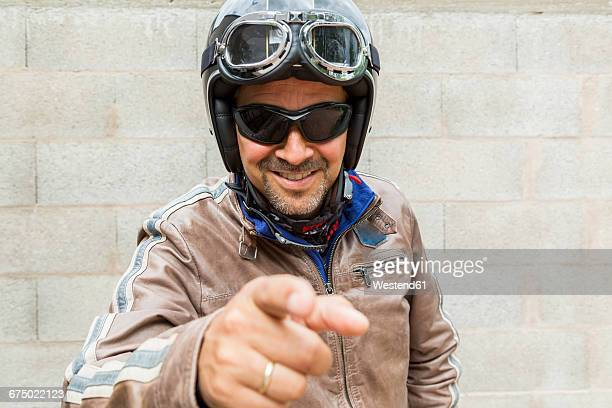 Smiling biker wearing sunglasses and helmet pointing on viewer