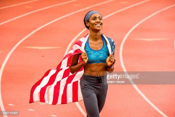 smiling black athlete holding american flag on track - オリンピック選手 ストックフォトと画像