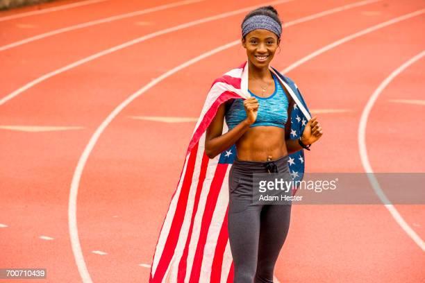 smiling black athlete posing with american flag on track - オリンピック選手 ストックフォトと画像