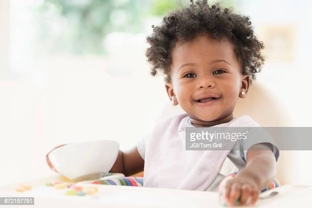 smiling black baby girl eating cereal from bowl in high chair - baby girls stock pictures, royalty-free photos & images