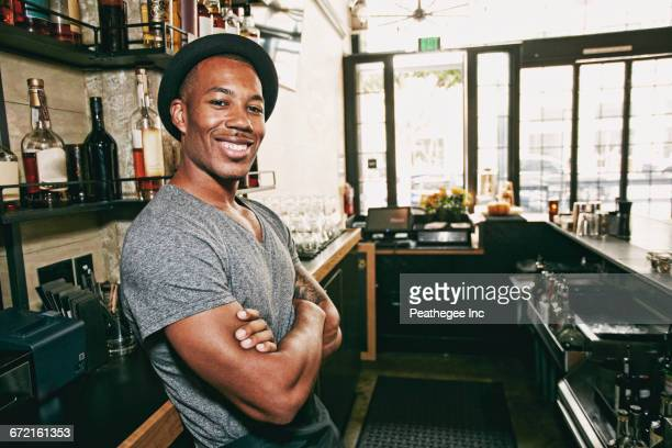 Smiling Black bartender relaxing behind bar