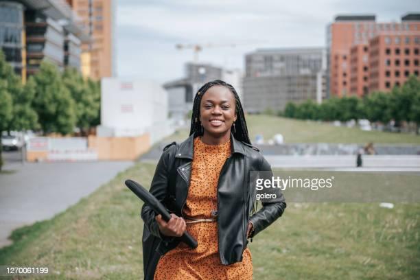 femme d'affaires noire de sourire dans le quartier d'affaires moderne à berlin - adulte d'âge moyen photos et images de collection
