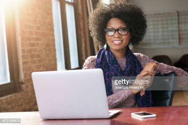 Smiling Black businesswoman posing with laptop at desk