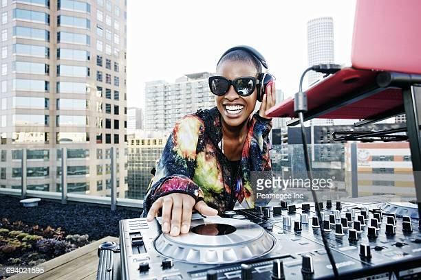 Smiling Black DJ on urban rooftop