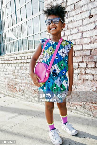 Smiling Black girl standing on sidewalk wearing dress and purse