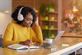 Smiling black girl with headset studying online, using laptop