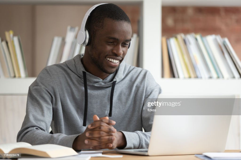 Smiling black male watch online training course at laptop : Stock Photo