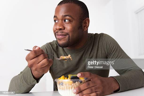 Smiling Black man eating breakfast