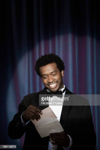 smiling black man in tuxedo announcing award winner - announcement message stock pictures, royalty-free photos & images
