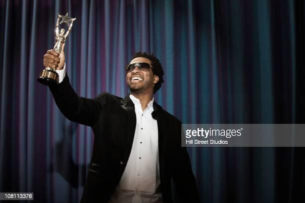 Smiling Black man in tuxedo holding award trophy