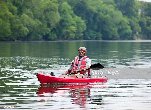 Smiling Black man kayaking on river