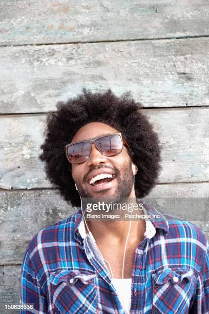 Smiling Black man listening to mp3 player
