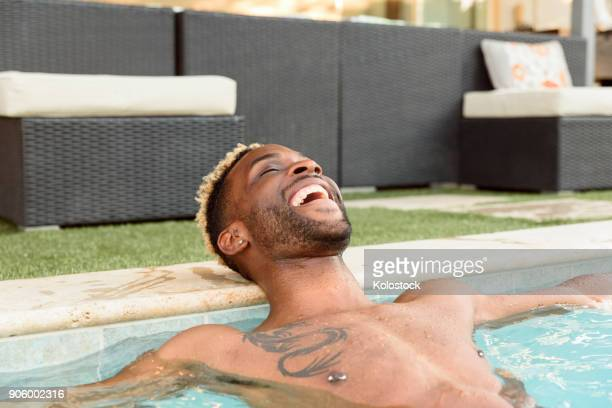 smiling black man relaxing in swimming pool - brustwarzen piercing stock-fotos und bilder