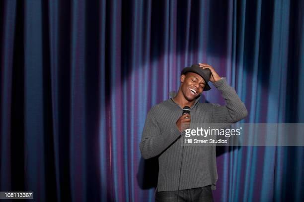 Smiling Black man singing into microphone