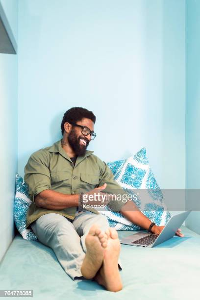 smiling black man sitting on bed pointing at laptop - barefoot black men stock pictures, royalty-free photos & images