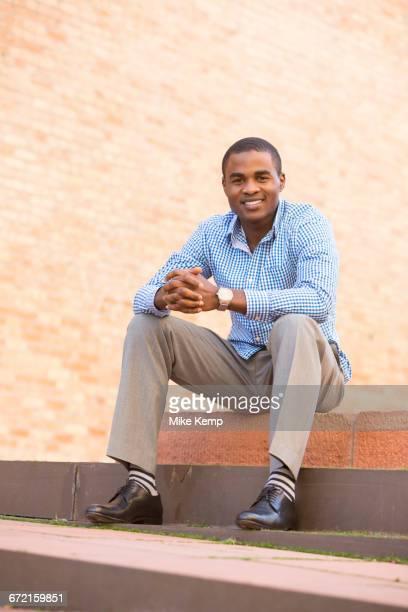 smiling black man sitting on staircase - só um homem - fotografias e filmes do acervo