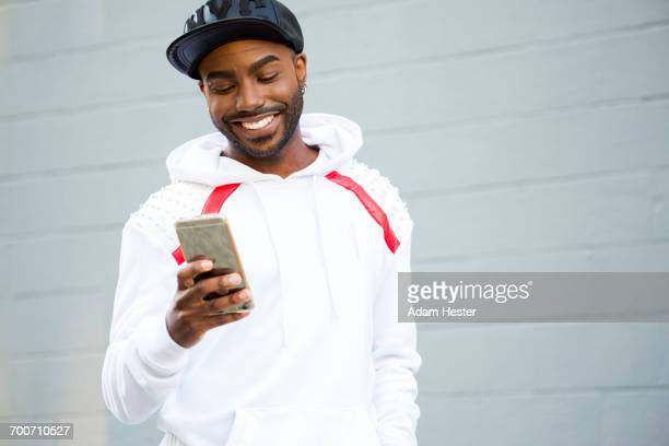 Smiling Black man texting on cell phone