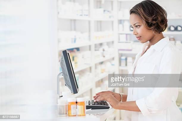 Smiling Black pharmacist using computer
