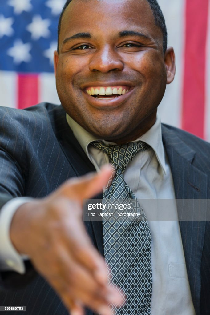 Smiling Black politician offering handshake : Stock Photo