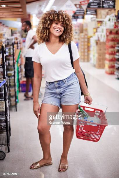 smiling black woman holding basket in grocery store - black shorts stock pictures, royalty-free photos & images