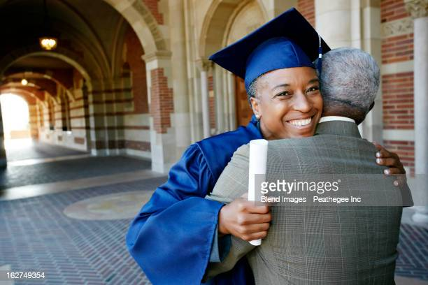 Smiling Black woman holding graduation diploma and hugging husband