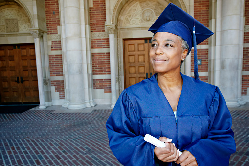 Smiling Black woman holding graduation diploma - gettyimageskorea