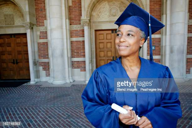 smiling black woman holding graduation diploma - corsi educativi per adulti foto e immagini stock
