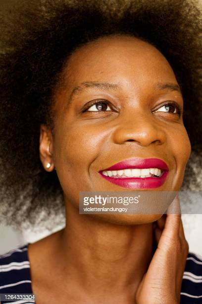 smiling black woman with afro hair wearing lipstick - african american culture stock pictures, royalty-free photos & images
