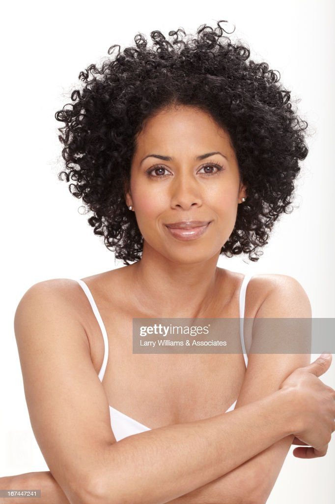 Smiling Black woman with arms crossed : Stock Photo