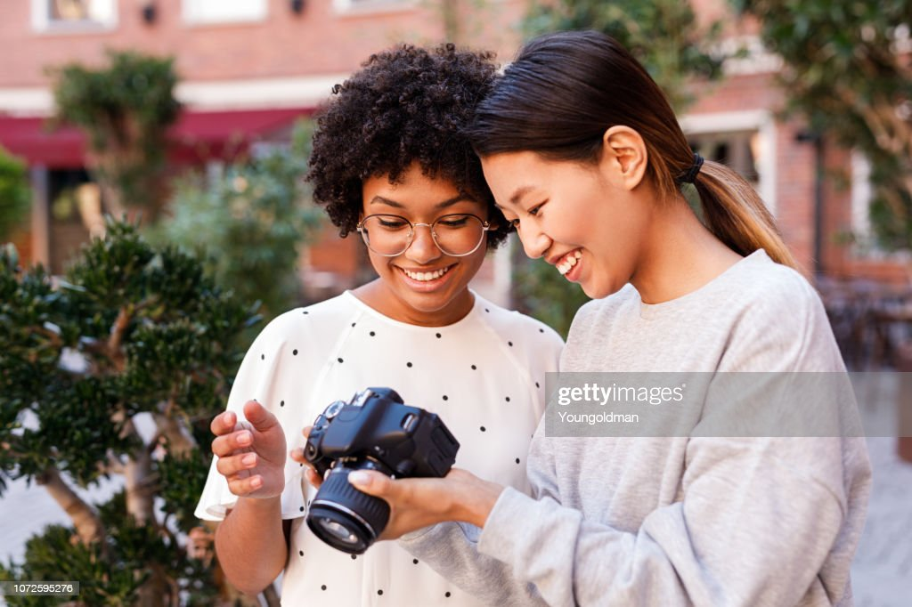Smiling blogger and her photographer looking at digital camera after shooting : Stock Photo
