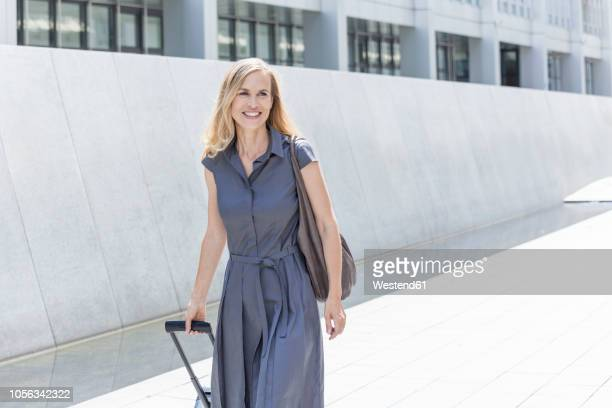 smiling blond businesswoman with wheeled luggage - grey dress stock pictures, royalty-free photos & images
