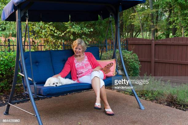 Smiling blond Caucasian woman in her 50's sits next to her little white Ocherese dog on a blue porch swing in the backyard on a summer day, Indiana, USA