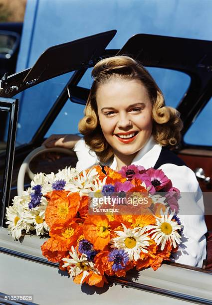 Smiling blond teen girl sitting in car driverõs seat holding colorful bouquet of flowers looking at camera, Los Angeles, California, 1949.