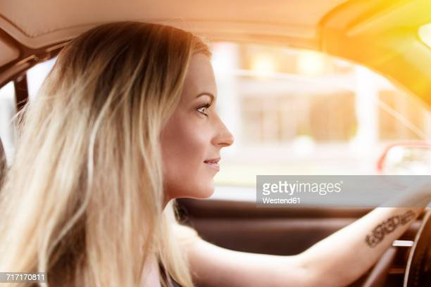 Smiling blond woman driving car