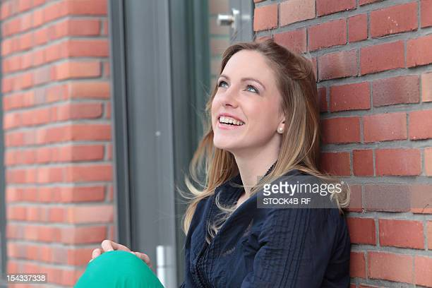 Smiling blond woman leaning against brick wall