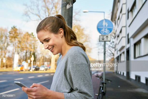 Smiling blond woman looking at cell phone