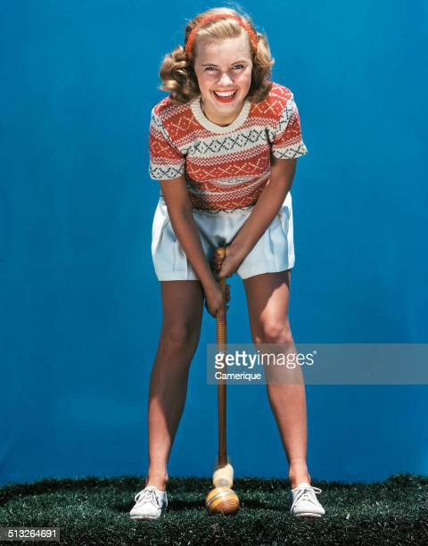 Smiling blond woman playing croquet hitting ball with mallet Los Angeles California 1949