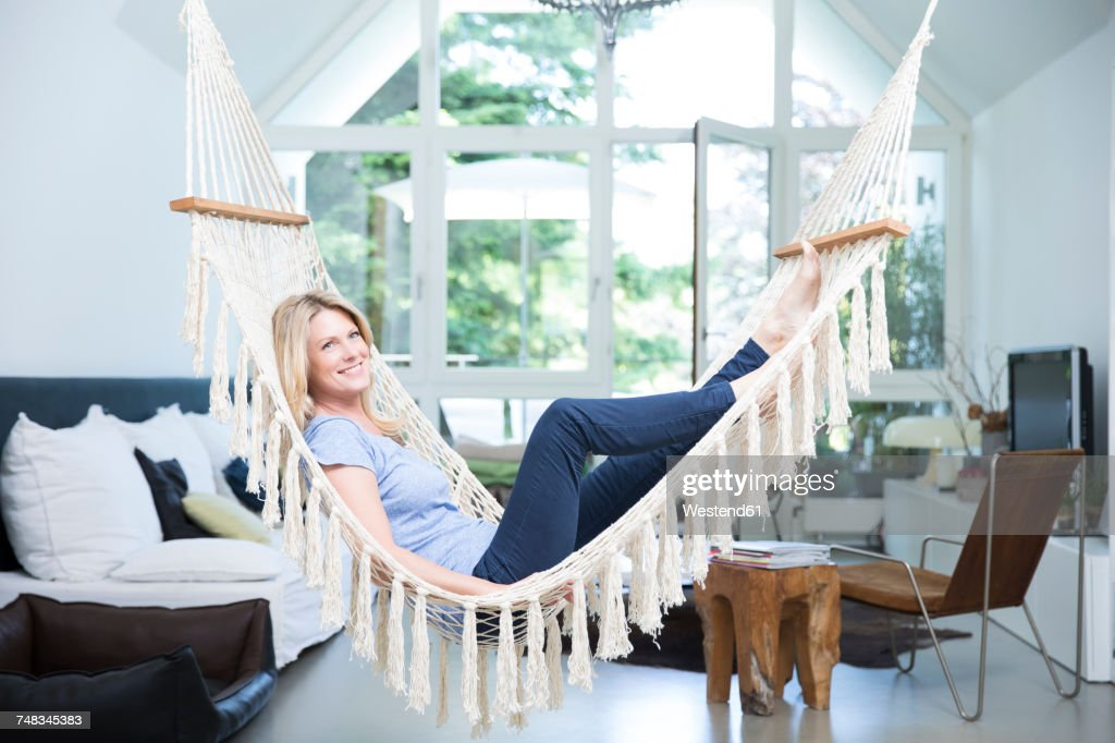Smiling Blond Woman Relaxing In Hammock In The Living Room