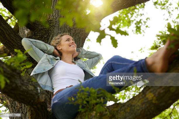 smiling blond woman relaxing in nature - s'évader du réel photos et images de collection
