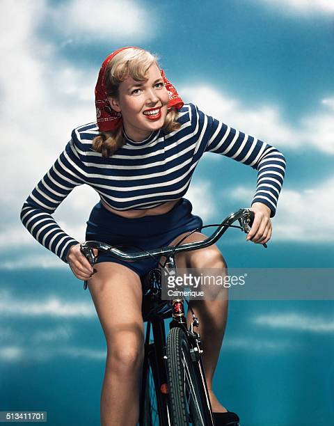 Smiling blond woman riding bicycle wearing red bandana blue and white striped shirt, Los Angeles, California, 1949.