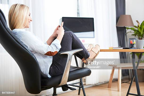 Smiling blond woman sitting at desk with feet up looking at her smartphone