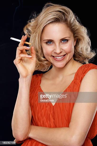 smiling blond woman smoking a cigarette - beautiful women smoking cigarettes stock photos and pictures