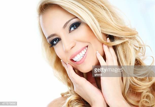 Smiling blond woman, studio portrait.