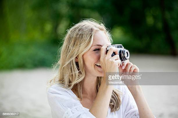 Smiling blond woman taking a photo with an old camera