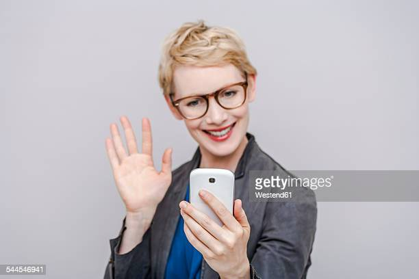 smiling blond woman taking a selfie with her smartphone - waving gesture stock photos and pictures