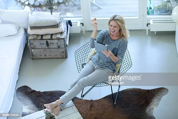 Smiling blond woman using digital tablet at home