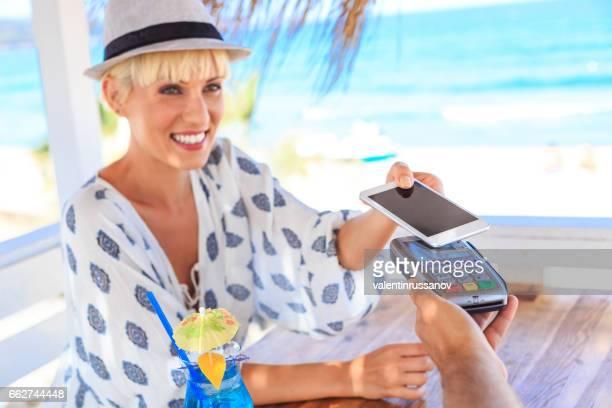 Lächelnde blonde Frau mit Smartphone für mobiles bezahlen