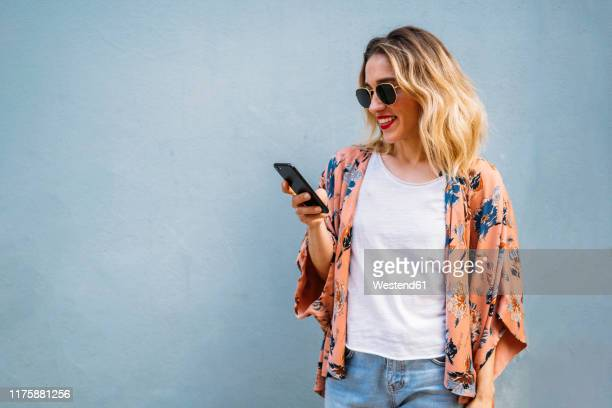 smiling blond woman using smartphone, blue background - junge frauen stock-fotos und bilder
